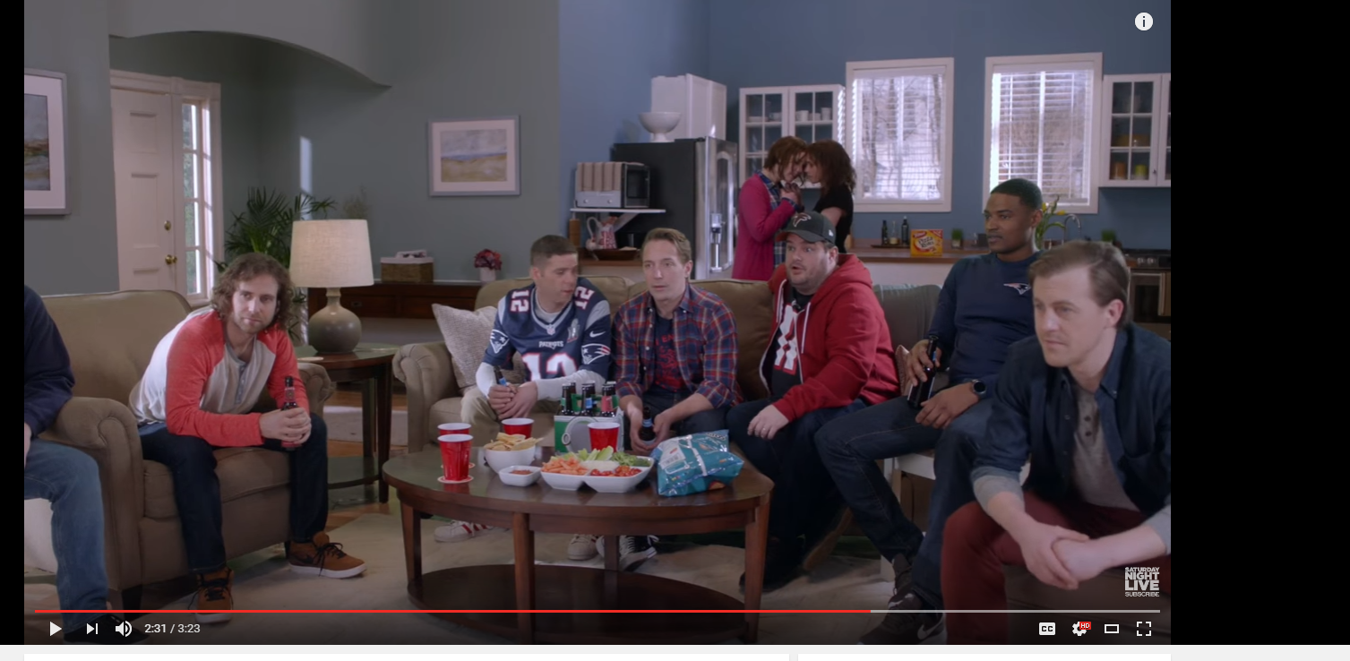 Image of five men in sports jerseys and casual wear sitting around a coffee table with chips, dip, and veggie platter, holding beers, while two women kiss in the kitchenette in the background