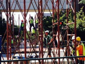 Workers assemble the framework for the pedestrian bridge over West Main Street.