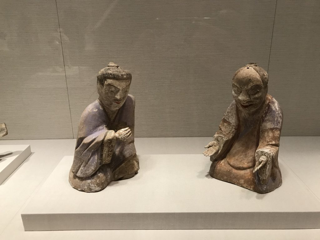 Two seated figurines wrapped up in a game of Liubo, without the board