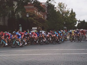 The peloton of the Men's U23 rounds Monument to Lombardy.