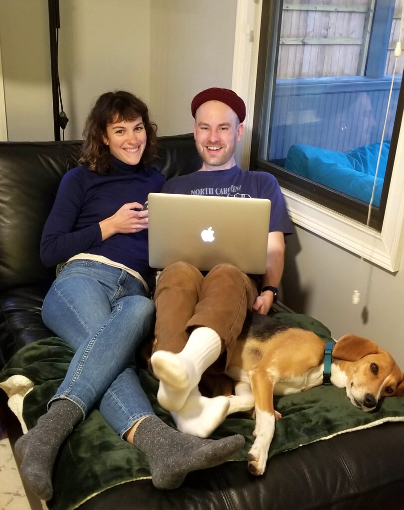 woman, man, sitting on a chair smiling while dog lies under their legs