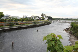 Fishermen stand tall in the River Corrib with the Galway weir closeby. The weir contains 16 hydraulic gates.