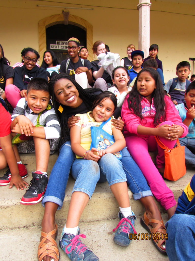 Cydni Gordon and other VCU Globe students pose with local children on the steps of the village municipal building in Teotitlán del Valle during a service-learning trip in 2014.