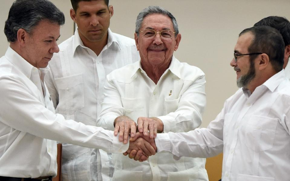 Colombian President Juan Manuel Santos, left, and FARC leader Timoleon Jimenez shake hands as Cuban President Raul Castro, centre holds their hands during a meeting in Havana, on September 23, 2015 AFP Luis Acosta(1)