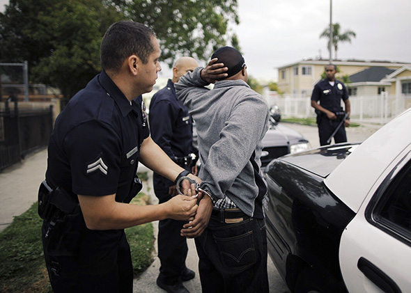 A young man being arrested by police with one hand behind his head