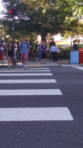 Students start to jaywalk on Main street.