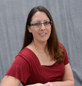 Photo of Amy Olex smiling wearing a red short-sleeved blouse and square-rimmed glasses