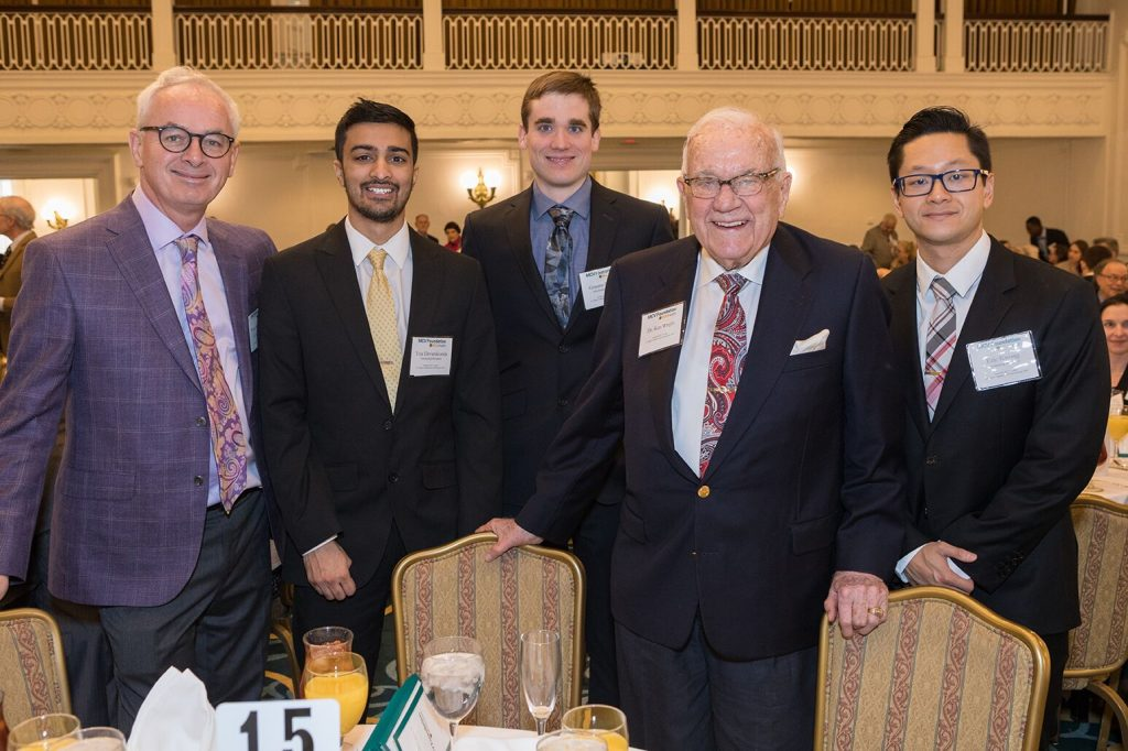 Dr. Buckley stands smiling with the three scholars and Mr. Wright in a ballroom. All are wearing suits.