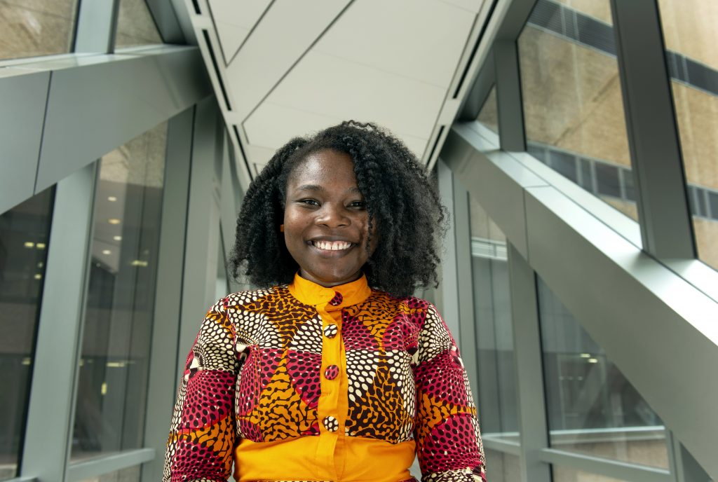 Dr. Agyemang smiles in the breezeway of a hospital wearing an orange and red patterned dress.