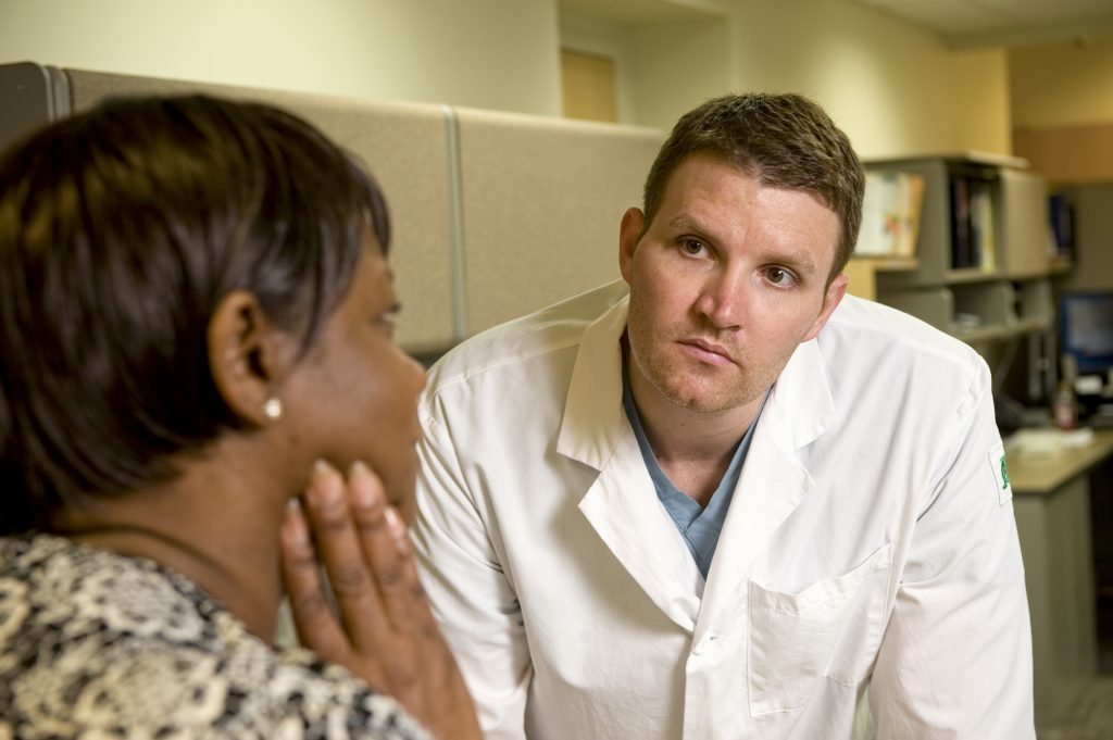 A doctor in a white lab coat talks with a patient.