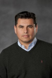 Headshot of Dr. Olivares-Navarrete wearing a black sweater over a blue collared shirt